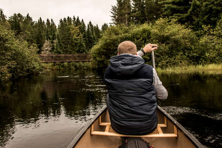 Man canoeing with Canoe on the lake of two rivers in the algonquin national park in Ontario Canada on cloudy day Stock Photo