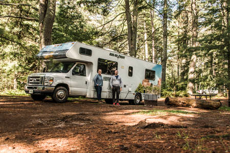 Canada Algonquin National Park 30.09.2017 couple in front of Parked RV camper Lake two rivers Campground Cruise America