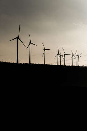 Black Silhouette of windturbines energy generator on amazing sunset at a wind farm in germany grey colored