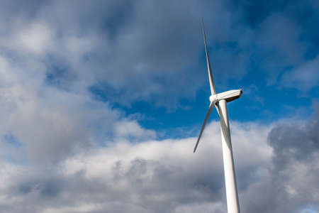 Isolated Silhouette of windturbine energy generator on blue cloudy sky at a wind farm in germany