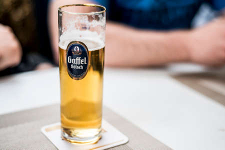 A glass of german beer on a table with gaffel koelsch company logo