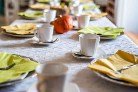 Beautiful festive dinner table colorful yellow fall helloween pumpkin decoration coffee mugs saucers plates and spoons