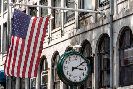 Boston, MA USA Shopping Mall Store front with american flag waving with a big clock beside it Imagens