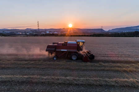 Aerial view of combine harvester harvesting an oats crop at sunset