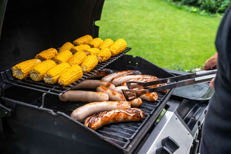 Freshly cooked sausages on a grill with corn close-up.