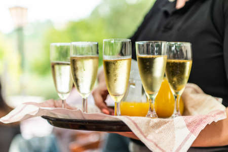 Champagne or sparkling wine in glasses in restaurant served by servant