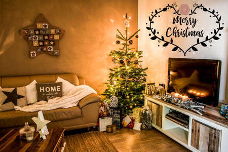 Merry Christmas beautiful living room tree setup aith gifts decorated at home textspace saying merry christmas Banco de Imagens