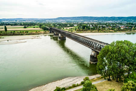 old train bridge near koblenz during Drought Germany, low water Rhine river influending water transport freight ships 免版税图像