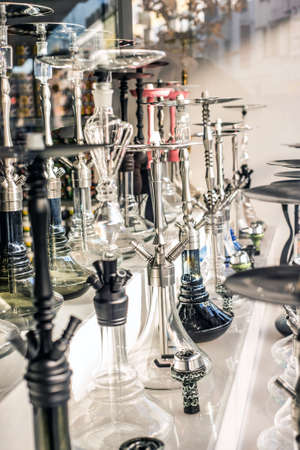 A lot of glass colorful hookahs shisha in a window shop smoking smoke