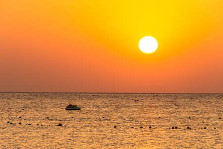boat silhouetts on the shores of the red sea at sunset in Makadi Bay Egypt golden colors