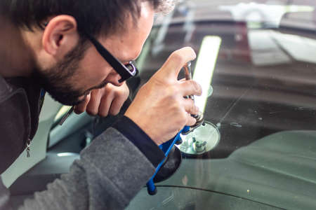 Koblenz Gerrmany 04.04.2018 man using repairing equipment to fix damaged cracked windshield at wintec company