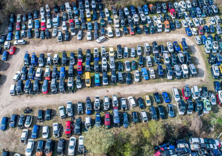Lines of crushed cars wreck in scrapyard before being shredded recyling