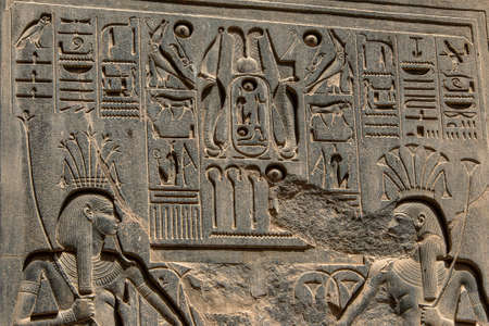 Ancient hieroglyphs and relief engravings carved into a stone wall at Luxor Temple of Amun-Ra