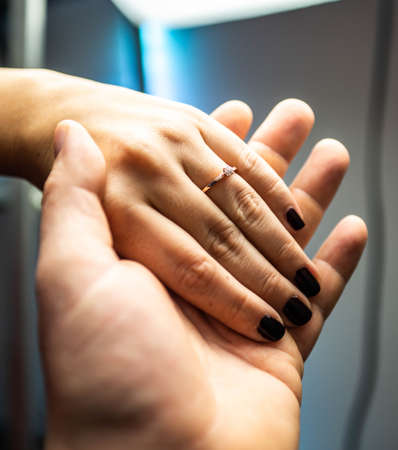 Closeup of hands man placing engagement ring in womans finger for love marriage