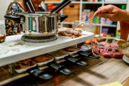 Schweizer oder niederländischer Raclette-Tisch gefüllt mit Zutaten für einen festlichen Abend wie Weihnachten oder Silvester Standard-Bild