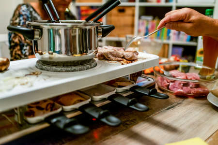 Swiss or Dutch raclette table filled with ingredients for a celebratory evening like Christmas or New Years Eve Stock Photo