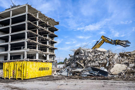 Building Demolition site Excavator hydraulic crasher and yellow container written word abbruch is german for demolition