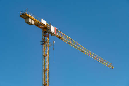 concrete construction yard building site yellow crane in front of blue sky background