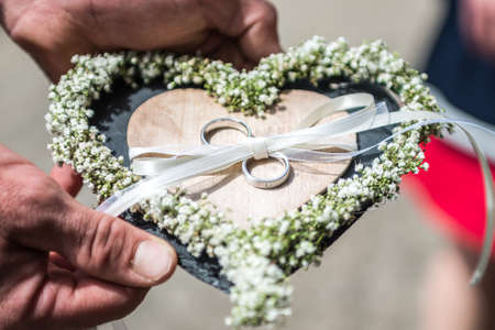 Beautiful wedding rings lie on stone surface against the stone background for a wedding couple with love Stock Photo