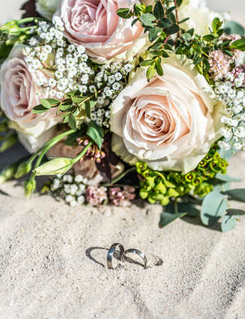 Beautiful wedding rings lie in the sand surface at the beach against the background of a bride bouquet of flowers