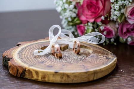 Beautiful wedding rings lie on wooden surface against the background of a bouquet of flowers and wedding couple Banque d'images - 131957494