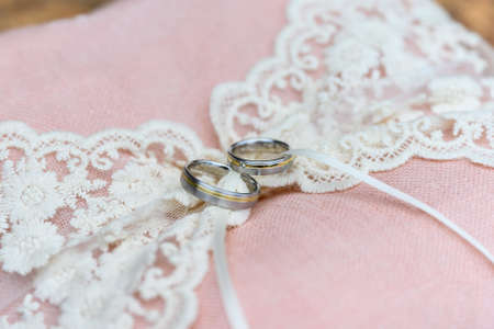 Close-up view of golden wedding rings on decorative pink ring pillow