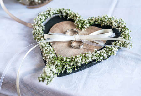 Beautiful wedding rings lie on white surface against the background of a bouquet of flowers and wedding couple