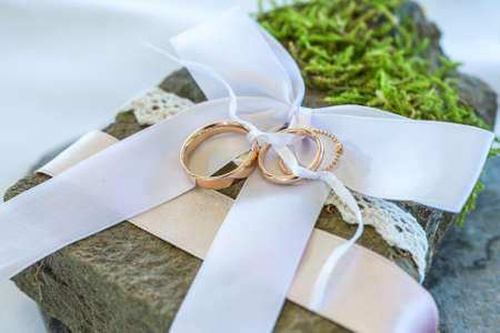 Beautiful wedding rings lie on stone surface against the white background for a wedding couple with love Banque d'images - 131957501