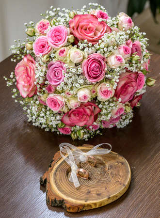 Beautiful wedding rings lie on wooden surface against the background of a bouquet of flowers and wedding couple