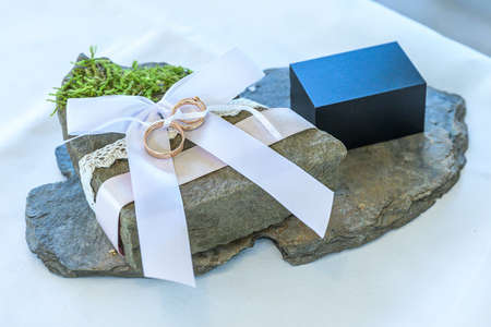 Beautiful wedding rings lie on stone surface against the white background for a wedding couple with love