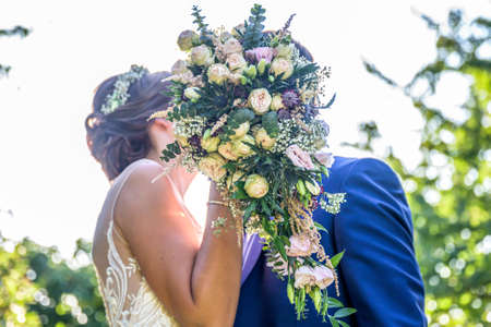 Side view of loving wedding couple kissing behind bouquet flower in garden wedding 免版税图像 - 140077545