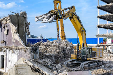 Building House destruction Demolition site Excavator with hydraulic crusher machine ruin house