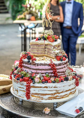 beautiful delicious Wedding cake in many tiers with fresh wild berries and fruits