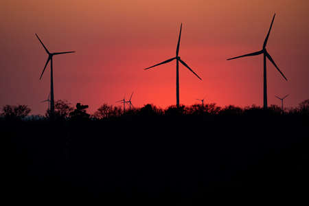 Black Silhouette of windturbines energy generator on amazing sunset at a wind farm in germany Stok Fotoğraf