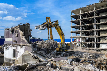 Building House Demolition site Excavator with hydraulic crasher machine and yellow container Foto de archivo