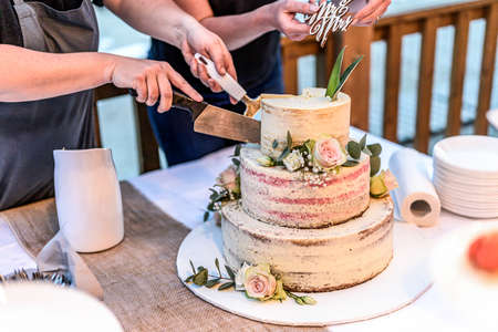 cutting a beautiful delicious Wedding cake in many tiers with fresh wild flowers and roses