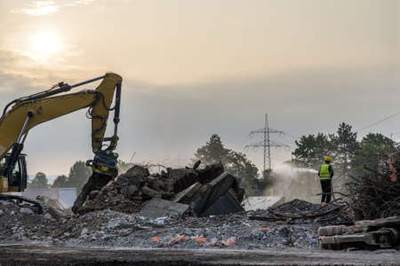Dawn time Building House Demolition site Excavator with hydraulic crasher machine and yellow container 版權商用圖片