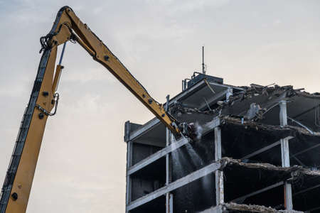 Building House destruction Demolition site Excavator with hydraulic crusher machine ruin house.