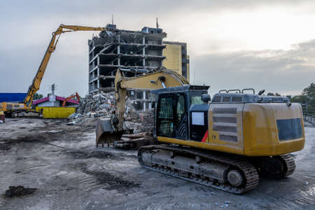 Dawn time Building House Demolition site Excavator with hydraulic crasher machine and yellow container.