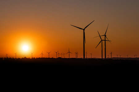 Black Silhouette of windturbines energy generator on an amazing sunset at a wind farm in germany 版權商用圖片