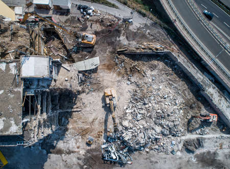 Aerial view of Building House Demolition and construction site Excavator with hydraulic crasher machine and yellow container
