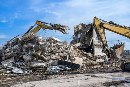 Building House Demolition site Excavator with hydraulic crasher machine and yellow container.