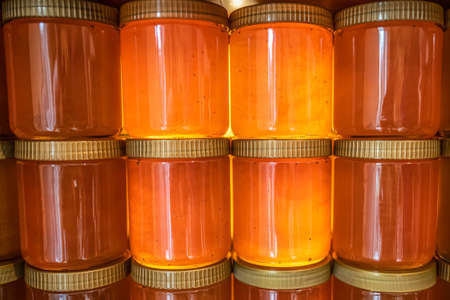 Tower and rows of Golden yellow honey in glass jar on wooden board Closeup Copy space