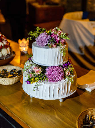 beautiful delicious Wedding cake in many tiers with fresh wild flowers and roses. 스톡 콘텐츠