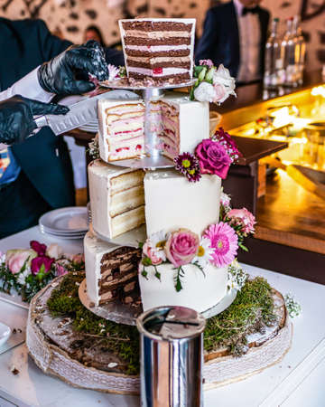 cutting a beautiful delicious Wedding cake in many tiers with fresh wild flowers and roses.