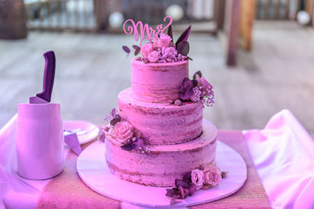 Beautiful wedding cake with cream With text MR MRS on top pink flowers roses. Archivio Fotografico
