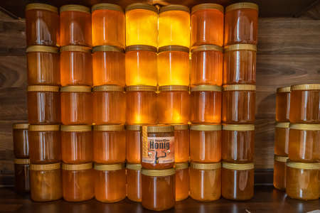 Koblenz Germany 14.06.2020 Tower and rows of Golden yellow honey in glass jar on wooden board Closeup Copy space