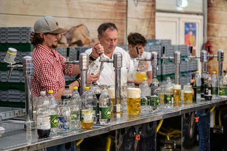 Koblenz Germany 27.09.2019 two man holding mugs glasses filling them with beer during Oktoberfest Editorial