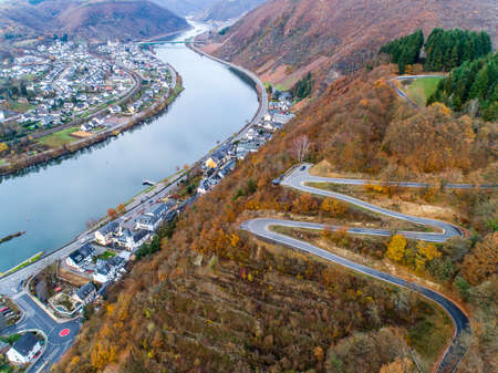 Seasons Concept winter or fall Aerial view Winding road serpentine mountain pass village Brodenbach Germany Standard-Bild