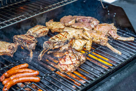 Tomahawk rib beef steak ans sausages on hot black grill with flames bbq